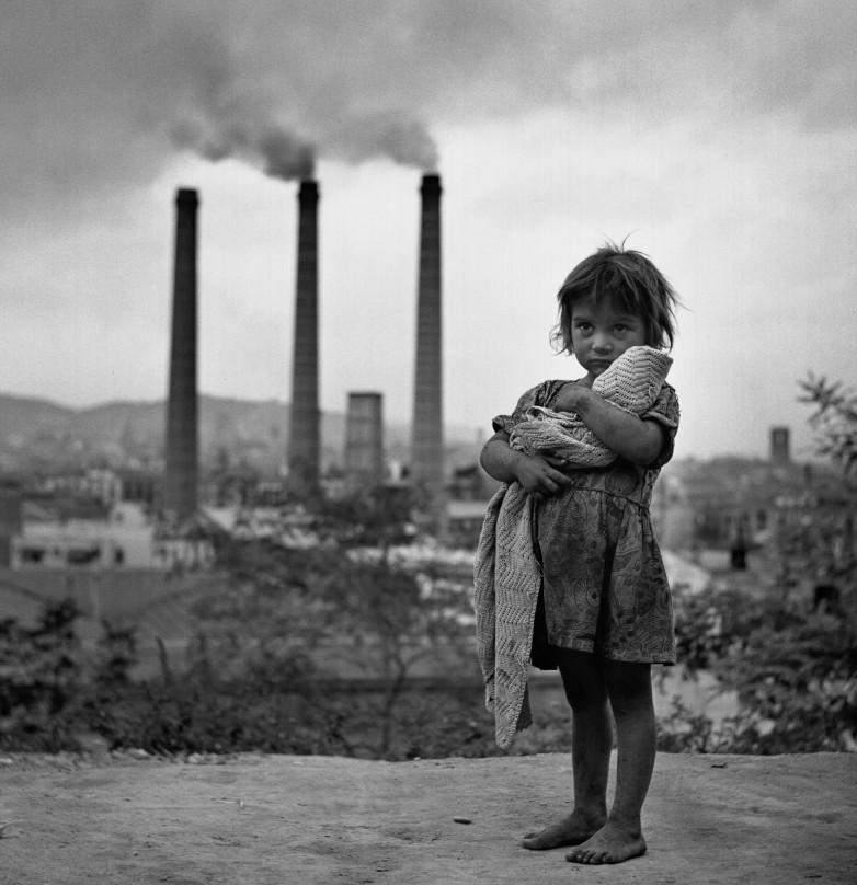 Fotografia di una bambina davanti alle fabbriche di Barcellona