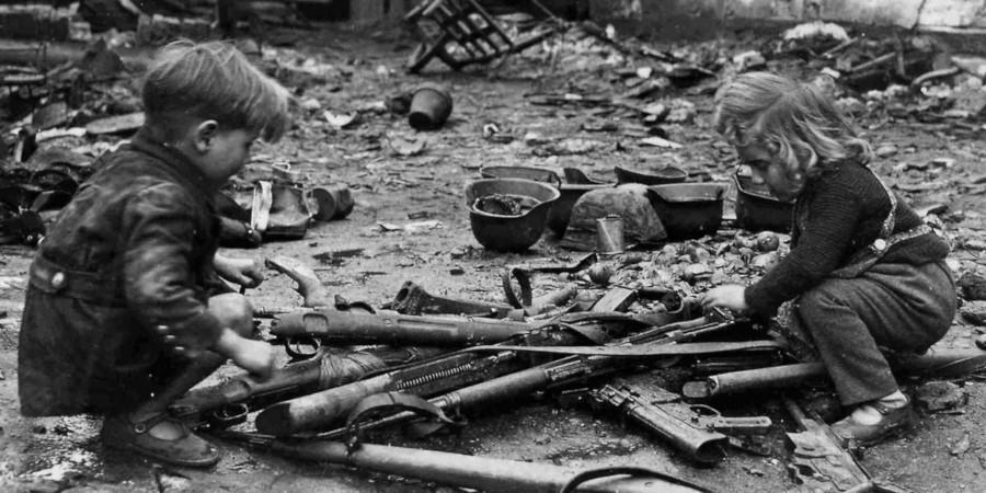 Due bambini giocano con dei resti di fucili.
