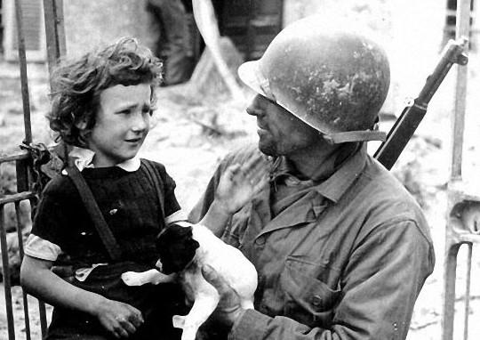 Schiaffo o carezza? Verso il soldato o il cagnolino? Chissà, la guerra è fatta di ambiguità.